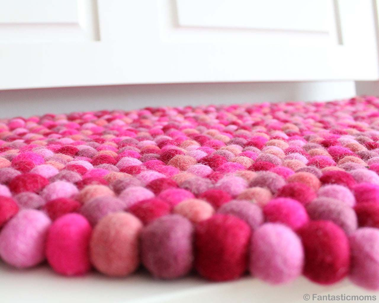 nepalian made modern pink red and orange felt ball small rug